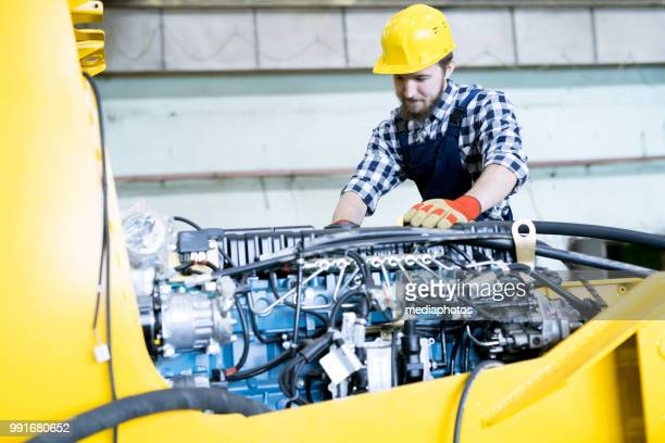 content concentrated young bearded repairing worker in yellow hardhat examining engine of tractor while working at industrial agricultural machinery plant - agricultural machinery stock pictures, royalty-free photos & images