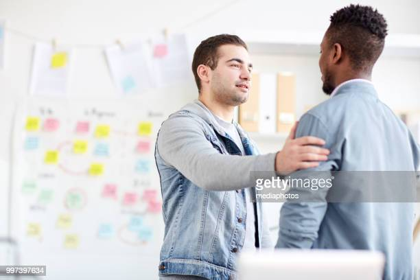 content confident handsome young man with stubble supporting office colleague and touching his shoulder while saying encouraging words - hand on shoulder stock pictures, royalty-free photos & images