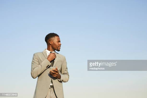 content confident stylish young african-american businessman in beige suit standing against clear sky and adjusting necktie while using smartphone - adjusting necktie stock pictures, royalty-free photos & images