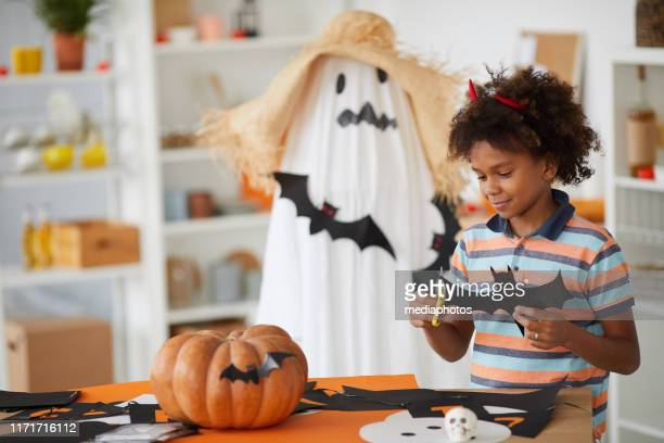 content curious afro-american boy in red horns standing at counter and cutting out rat of paper - halloween decoration stock pictures, royalty-free photos & images