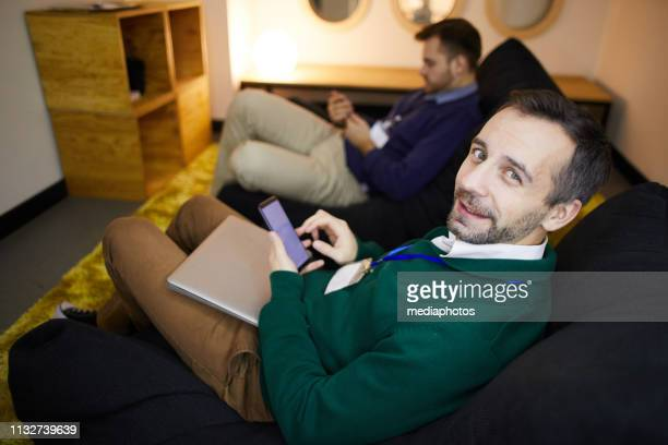 Content handsome businessman with beard sitting in bean bag and using gadget while relaxing in lounge zone