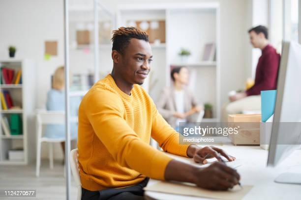 Content handsome young black guy with Afro hairstyle sitting at table and making notes while working with computer