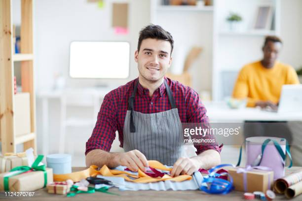 Content handsome young man in apron sitting at table and looking at camera while working in creative workshop