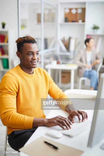 Content handsome young programmer in yellow sweater sitting at table and typing on computer keyboard while working in modern office