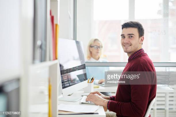 Content handsome young software engineer with stubble sitting at table and typing on computer keyboard while composing code in modern office