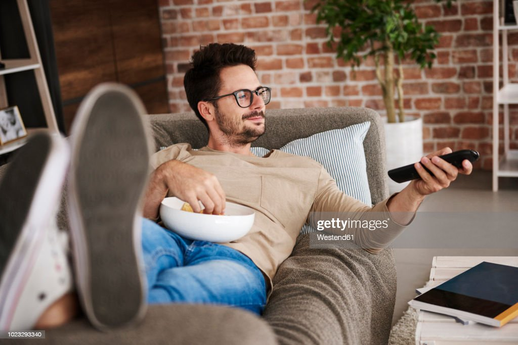 Content man lying on couch at home with bowl of potato chips watching TV : Stock Photo