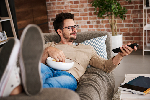 Content man lying on couch at home with bowl of potato chips watching TV - gettyimageskorea