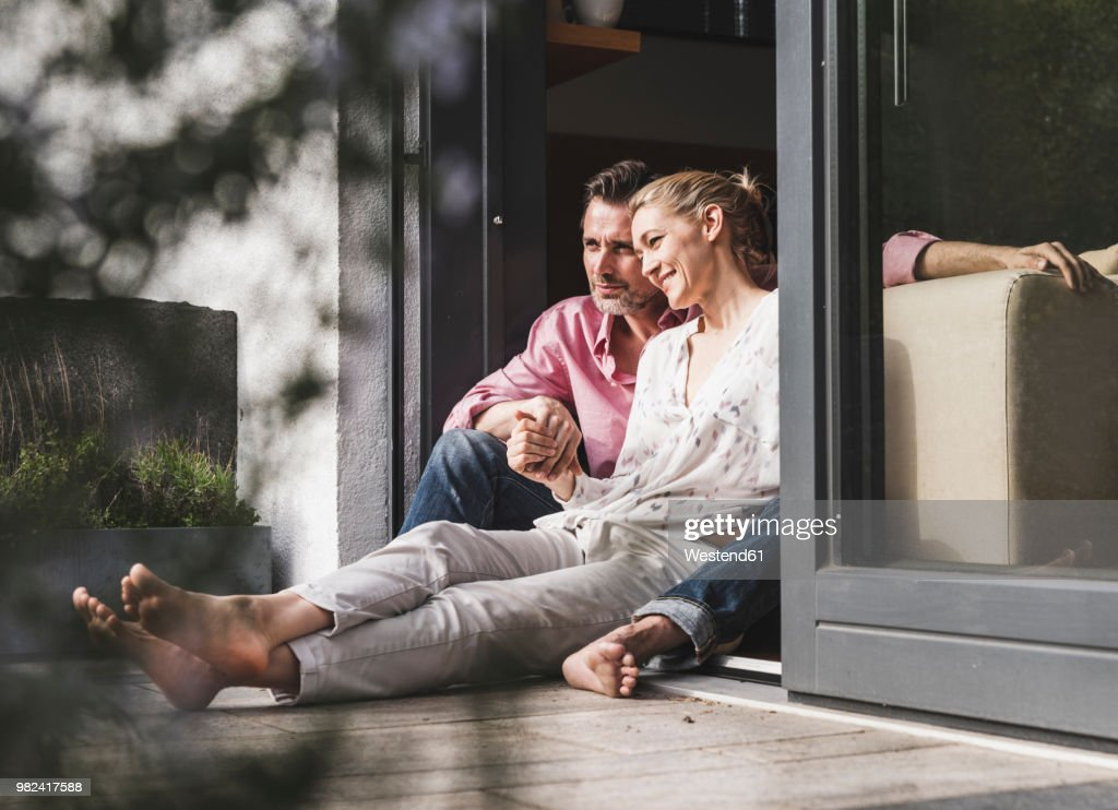 Content mature couple relaxing together at open terrace door : Stock Photo