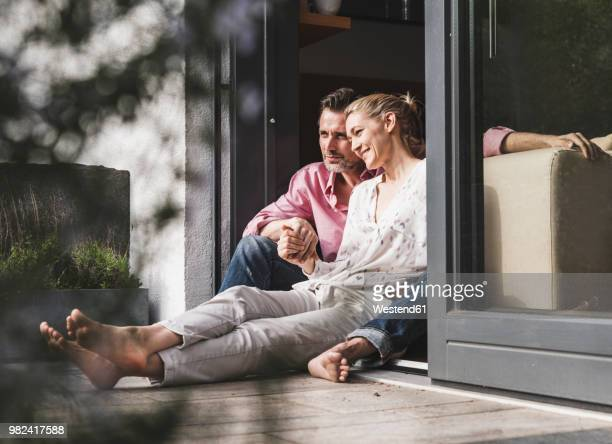 content mature couple relaxing together at open terrace door - couple stock-fotos und bilder