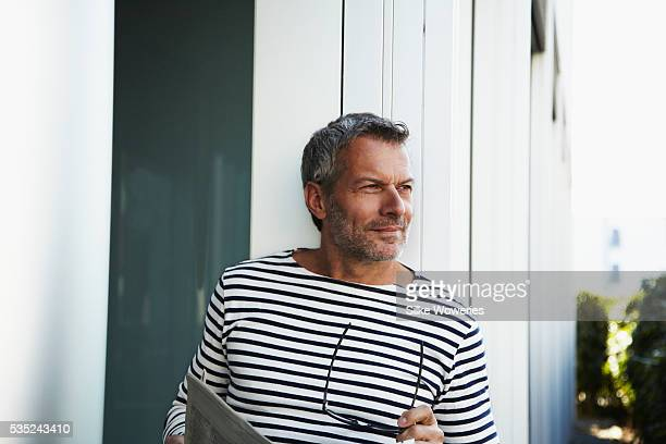 content middle-aged man holding eye glasses - handsome 50 year old men stock photos and pictures
