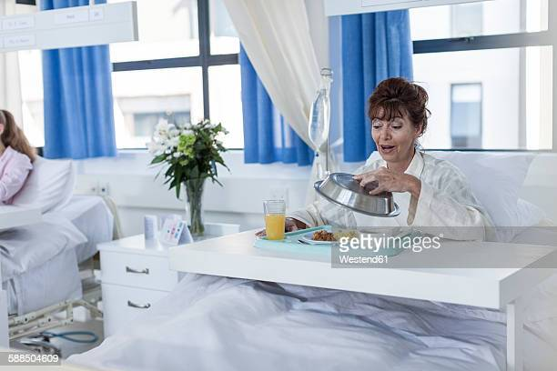 Content patient in hospital bed having lunch