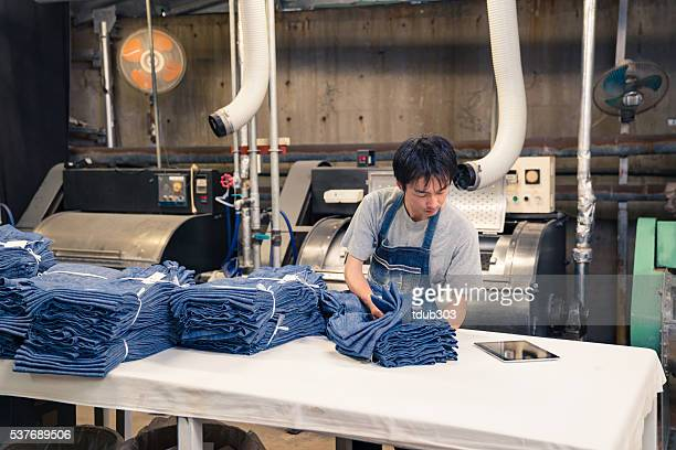 content textile industry worker washing and sorting garments before shipping