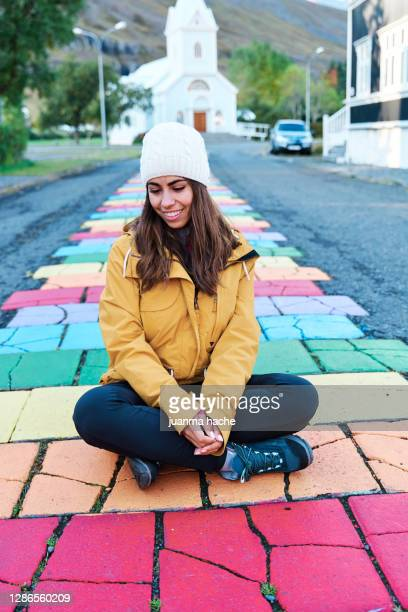 content traveling woman on colorful street in village - ショッキングピンク ストックフォトと画像