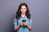 Content trendy cheerful nice cute adorable lovely attractive brunette girl with wavy hair in casual denim shirt, typing in phone, isolated over grey background