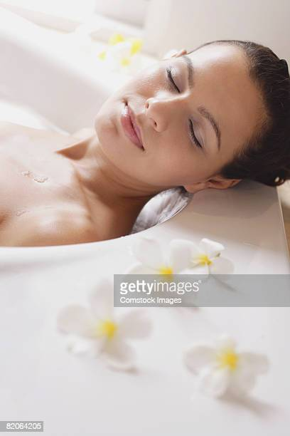 Content woman in bathtub with flowers