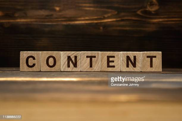 content word on wooden blocks - contente imagens e fotografias de stock