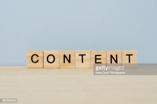 content word on wooden tile block - tevreden stockfoto's en -beelden