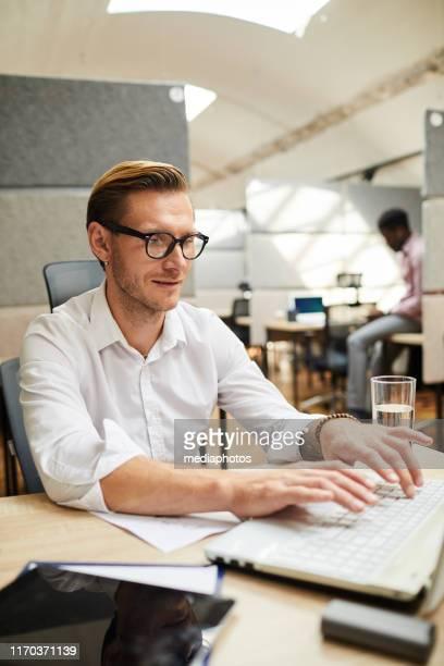 inhoud jonge man in brillen zittend op bureau en typen op laptop tijdens het werken aan artikel voor sociale media - typen stockfoto's en -beelden