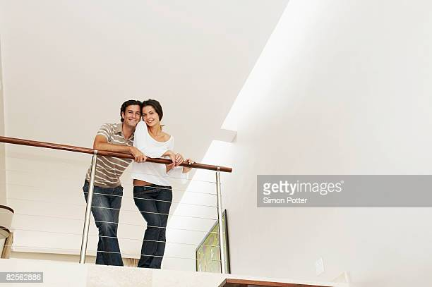 Contented couple lean over balcony