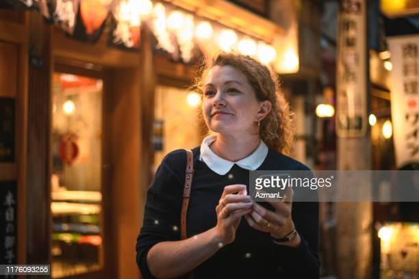 zufriedene touristin mit smartphone in tokio bei nacht - shinjuku bezirk stock-fotos und bilder