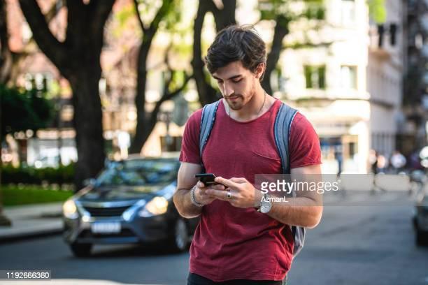 スマートフォンで満足した男性観光客チェックの方向 - 接近する ストックフォトと画像