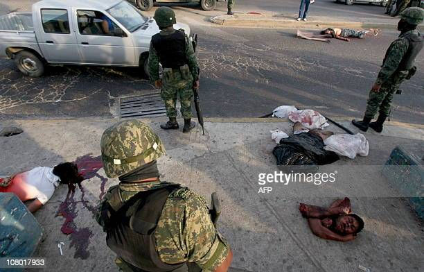 CONTENTMembers of Mexican Navy surround one of the three corpses one decapitated and partially dismembered found on the AcapulcoMexico road in the...