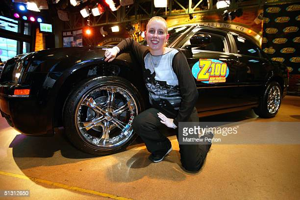 Contest Winner Melissa Kennedy of Mahopac New York poses with her new Chrysler 300 sedan as part of the Z100 Pimp My Summer Contest at Times Square...