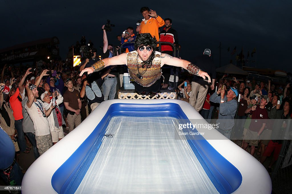 A contestant dives into a pool of water in the infield after winning a moon pie eating contest following qualifying for the NASCAR Nationwide Series Aaron's 312 at Talladega Superspeedway on May 2, 2014 in Talladega, Alabama.