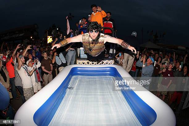 Contestant dives into a pool of water in the infield after winning a moon pie eating contest following qualifying for the NASCAR Nationwide Series...