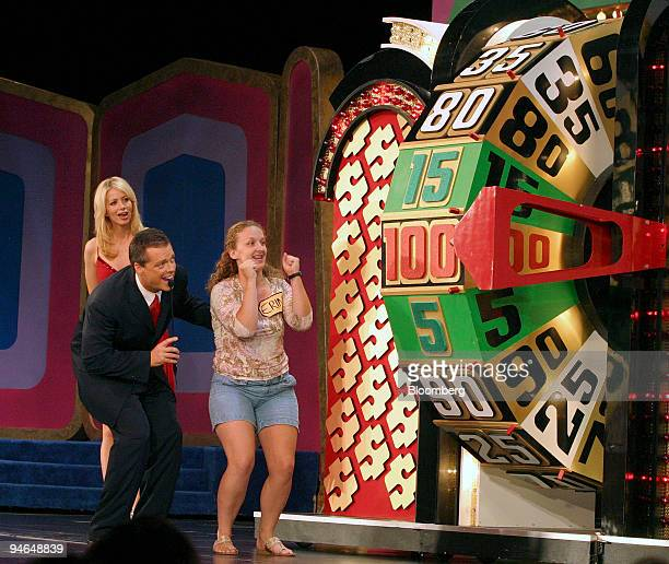 Contestant Erin gestures as she watches the money wheel with host Todd Newton at the Price is Right Live stage show at Bally's Resort in Las Vegas...
