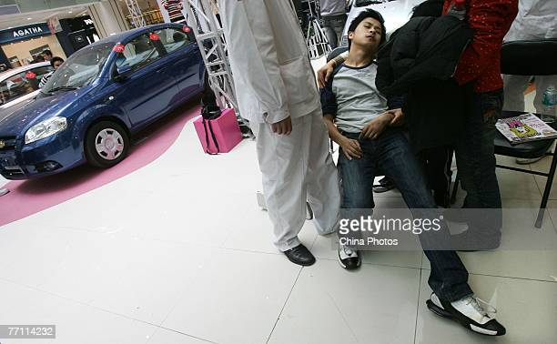 A contestant faints after 26 hours of a carkissing competition held in a department store September 30 2007 in Beijing China The contestants are...