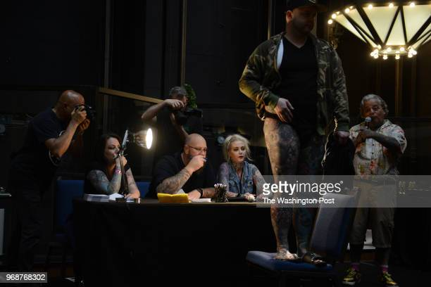 Contestant Kenton Mann is judged by judges Candy Dunbar Jason Sloan and Elyse Fox for the best overall tattoos during the Nation's Tattoo Expo at the...