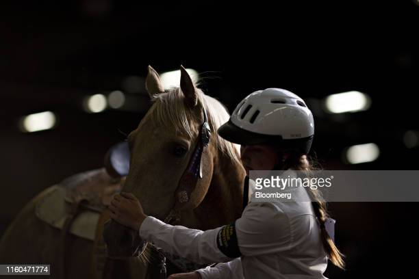 A contestant leads a horse from the Exhibition Center after competing in a Future Farmers of America barrel racing event at the Iowa State Fair in...