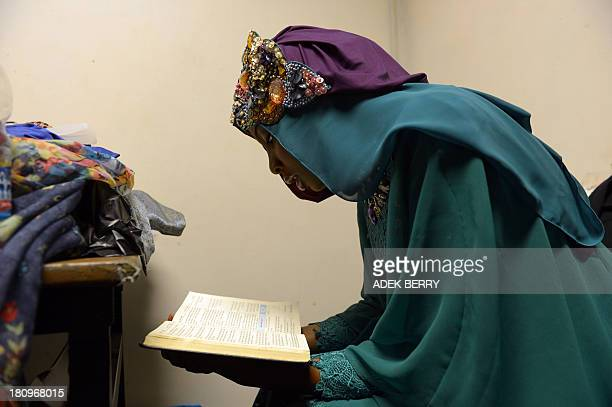 Contestant of the Muslimah World 2013 Obabiyi Aishah Ajibola of Nigeria recites a copy of the Koran while contestants wait for a grand final during...