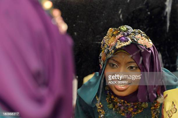 Contestant of the Muslimah World 2013 Obabiyi Aishah Ajibola of Nigeria checks her makeup in a mirror while contestants wait for a grand final during...