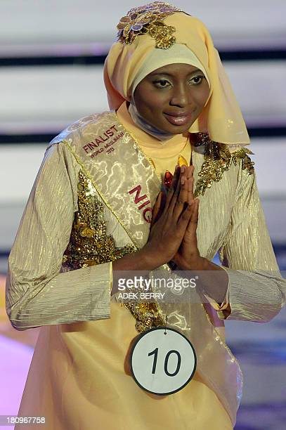 Contestant of the Muslimah World 2013 Obabiyi Aishah Ajibola of Nigeria gestures to a judge panel during the Muslimah World competition in Jakarta on...