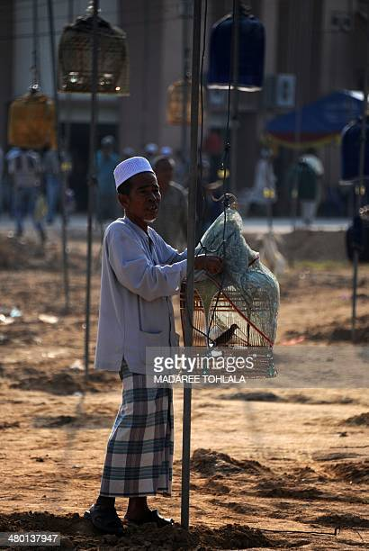 A contestant prepares to hang his bird cage on a pole during a birdsinging contest in the Rueso district in Thailand's southern province of...