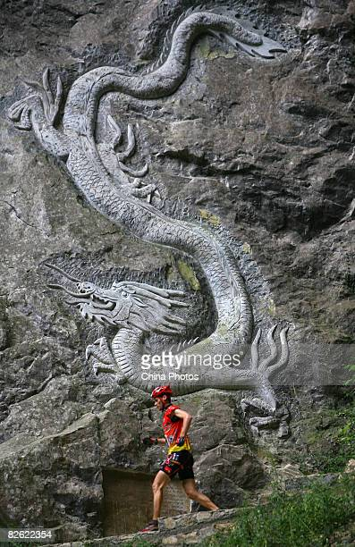 A contestant runs past a dragon engraved on the crag as he competes during the caving session of the Wulong Mountain Quest on September 1 2008 in...