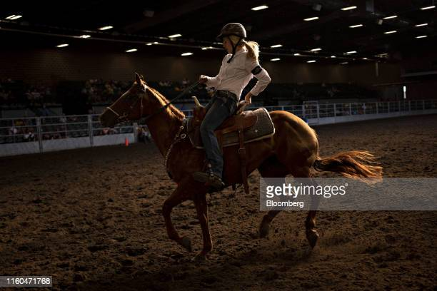 A contestant slows a horse during a during a Future Farmers of America barrel racing event at the Iowa State Fair in Des Moines Iowa US on Thursday...