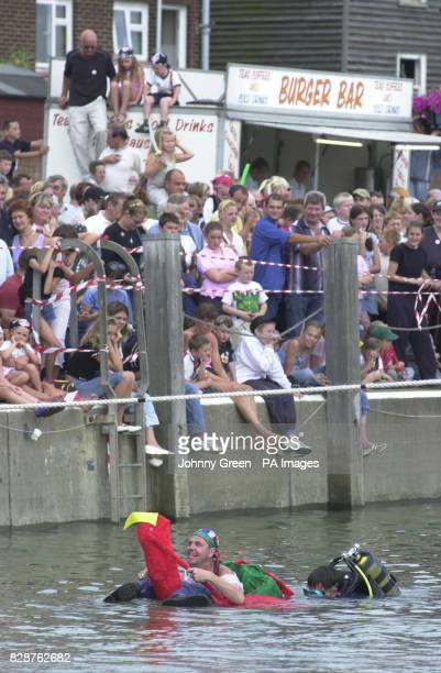 A contestant swims ashore after taking part in the 7th World Walking the Plank Championships in Queenborough on the Isle of Sheppey in Kent A...