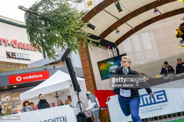 A contestant throws a fir tree at the second Christmas Tree Long Throw Challenge to happen in Wolfsburg Germany 6 January 2018 Photo Philipp von...
