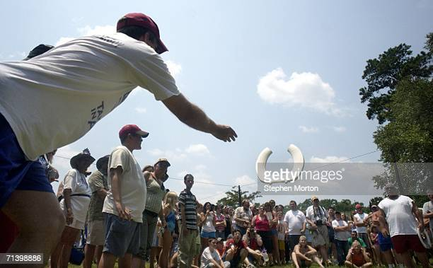 A contestant throws a plastic toilet seat during the Redneck Horseshoes contest July 8 2006 in Dublin Georgia Started in 1996 as a spoof for the...
