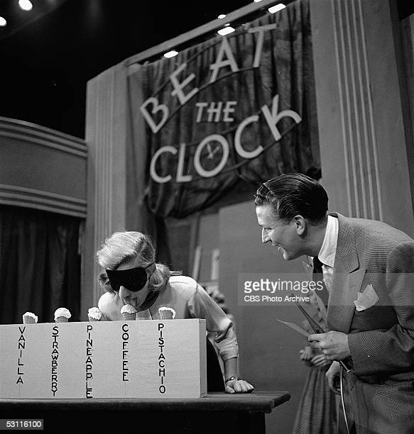 A contestant wears a blindfold and licks an ice cream cone as American game show host Bud Collyer smiles an looks on during an episode of the CBS...