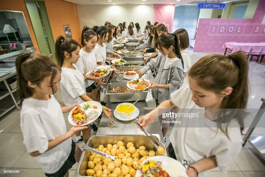 Contestants choose food inside the cafeteria set during the production of the 'Idol School' reality television show by CJ E&M Corp.at the Yangpyeong English School in Yangpyeong, South Korea, on Thursday, June 29, 2017. Endless repetition, tear-inducing critiques from coaches, smile practice, and psychological counselling are plot points in an 11-week reality TV show documenting the creation of a teeny-bopper singing group. Idol School, which began airing in July, is part of a corporate push to turn Korean pop music into a global phenomenon. Photographer: Jean Chung/Bloomber