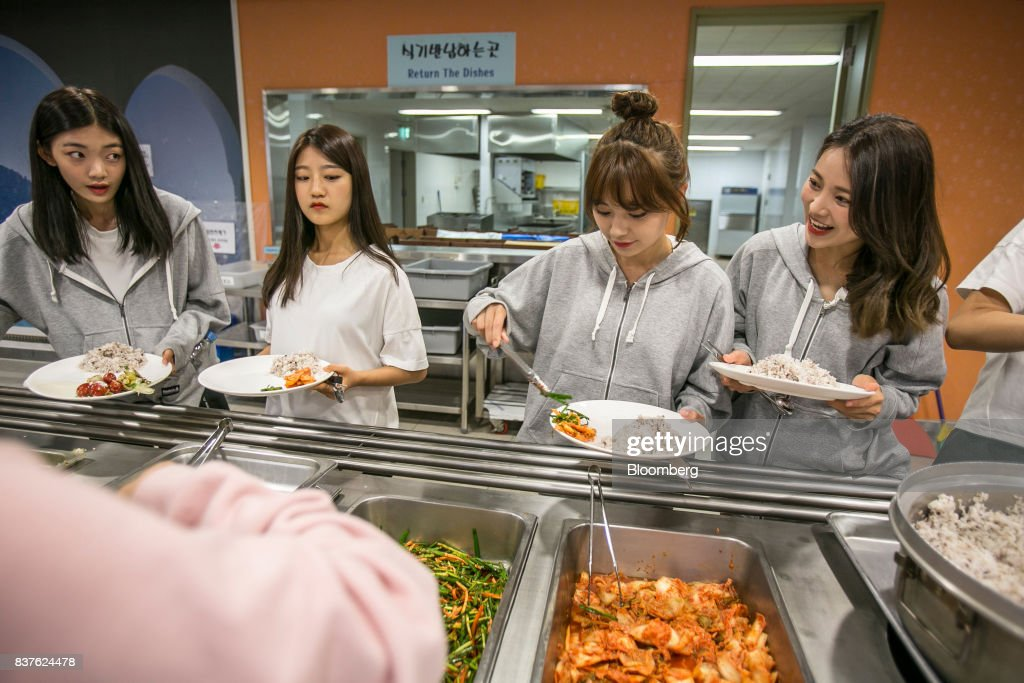 Contestants choose food inside the cafeteria set during the production of the 'Idol School' reality television show by CJ E&M Corp. at the Yangpyeong English School in Yangpyeong, South Korea, on Thursday, June 29, 2017. Endless repetition, tear-inducing critiques from coaches, smile practice, and psychological counselling are plot points in an 11-week reality TV show documenting the creation of a teeny-bopper singing group. Idol School, which began airing in July, is part of a corporate push to turn Korean pop music into a global phenomenon. Photographer: Jean Chung/Bloomber