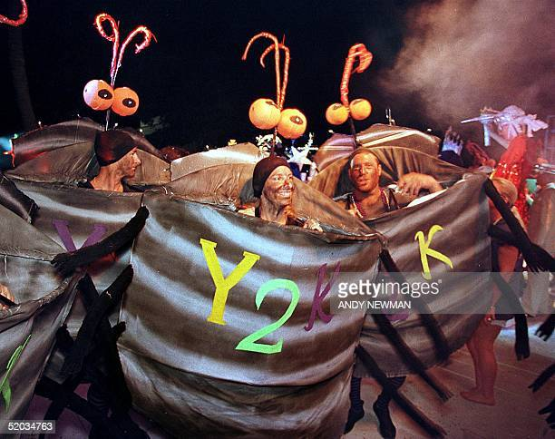 Contestants costumed as Y2K Bugs dance and prance during the Pier House Pretenders in Paradise Costume Competition early 29 October 1999 as part of...