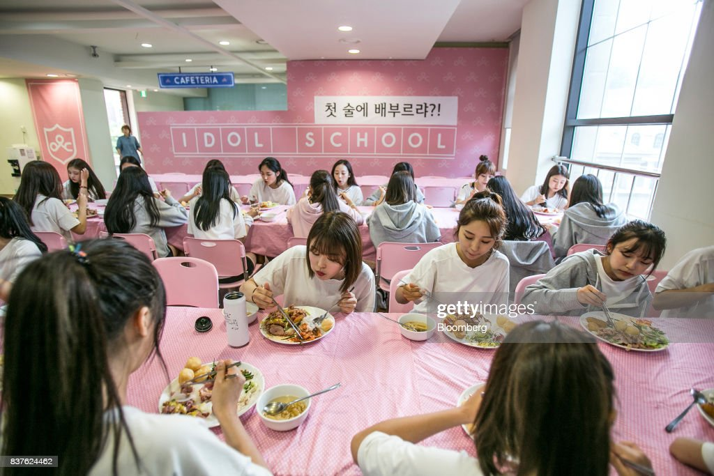 Contestants eat inside the cafeteria set during the production of the 'Idol School' reality television show by CJ E&M Corp.at the Yangpyeong English School in Yangpyeong, South Korea, on Thursday, June 29, 2017. Endless repetition, tear-inducing critiques from coaches, smile practice, and psychological counselling are plot points in an 11-week reality TV show documenting the creation of a teeny-bopper singing group. Idol School, which began airing in July, is part of a corporate push to turn Korean pop music into a global phenomenon. Photographer: Jean Chung/Bloomber