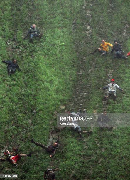 Contestants in the men's race chase a Double Gloucester Cheese down the steep gradient of Cooper's Hill in pouring rain during the annual Bank...