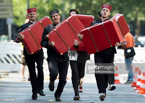 Contestants in the porter event react as they carry a suitcase during the annual Berlin Waiters' Race in Berlin Germany on August 4 2013 The...