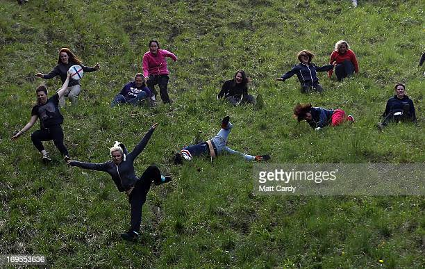 Contestants in the women's race chase a replica Double Gloucester Cheese down the steep gradient of Cooper's Hill during the annual Bank Holiday...